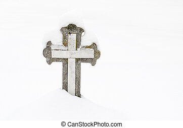Christian stone cross in the cemetery, covered with snow .