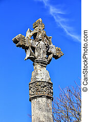 Christian stone cross with blue sky background