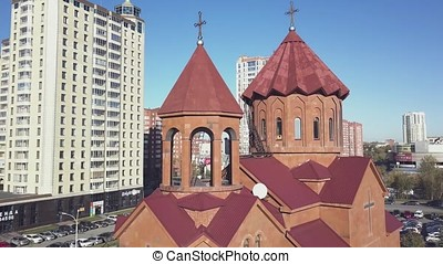 Christian temple made of red bricks with city background. Russian Orthodox Church in the city, red brick against the blue sky