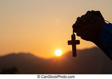 Christian woman praying on holy cross in the morning, teenager woman hand with cross praying,Hands folded in prayer in church concept for faith, spirituality and religion