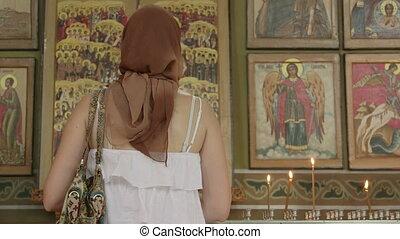 Christian women prayer before icons in Orthodox Church
