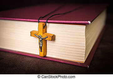Christian wooden cross necklace on holy Bible