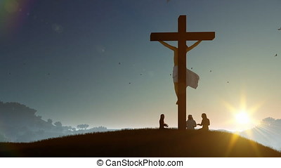 Christians praying at Jesus cross at sunset, zoom out