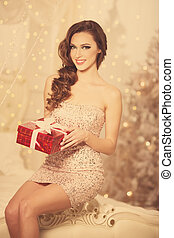 Christmans party, winter holidays woman with gift box. New year girl. christmas tree in interior background.