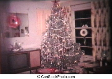A cool shot of a festive living room decked out with Christmas tree, gifts, presents and all the trimmings ready for Christmas. (Scan from archival 8mm film)