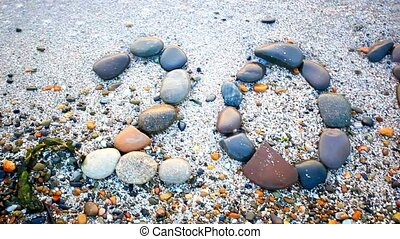 Christmas 2015 made of small stones on the sandy beach.