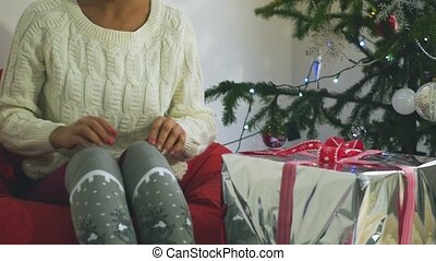 Christmas: A woman near the tree on the eve of the holiday.