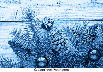 Christmas accessories in blue and fir branches on wooden background in classic blue trendy color of the year 2020.