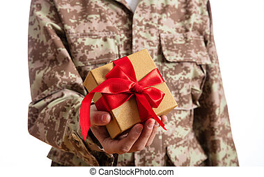 Young soldier holding a christmas gift standing on white background