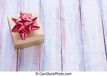 Christmas and happy new year brown gift box and red ribbon with tag on wood background.