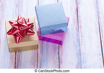 Christmas and happy new year gift box and red ribbon with tag on wood background.