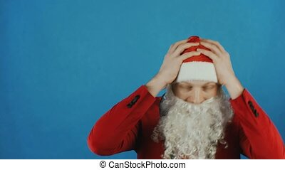 Christmas and New year 2019, man like a Santa surprised and holds his head by hands, on blue background