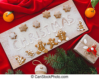 Christmas and New Year background. Composition of gifts, Christmas tree decorations and branches, and gingerbread men on a wooden board, on red cloth