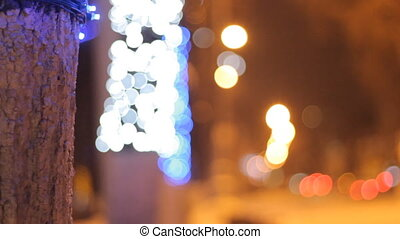 Christmas and New Year background. Abstract blurred bokeh. Garland on a tree. With cars.
