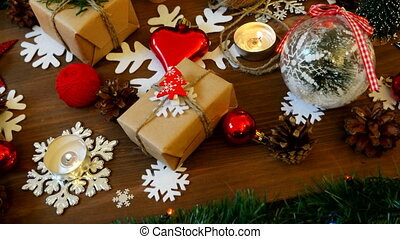 Christmas and New year background with presents, lights, candles and different decorations. Gift in craft paper with red fir tree.