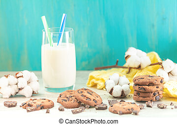 Christmas and New Year composition with delicious chocolate cookies and glass of milk, cotton plant flower branch