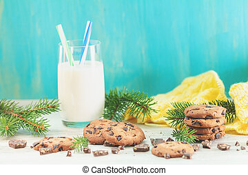 Christmas and New Year composition with delicious chocolate cookies and glass of milk, spruce branches and pine cones