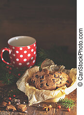 Christmas and New Year composition with delicious chocolate cookies, peanuts and cup of coffee or tea, spruce branches and pine cones