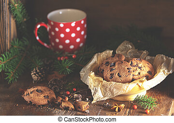 Christmas and New Year composition with delicious chocolate cookies, peanuts and cup of coffee or tea