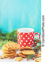 Christmas and New Year composition with delicious peanut cookies, peanuts and cup of coffee or tea, spruce branches and pine cones