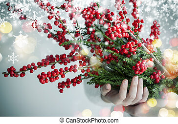 Christmas and new year concept design of woman hands holding ilex verticillata or winterberry with snow and light bokeh