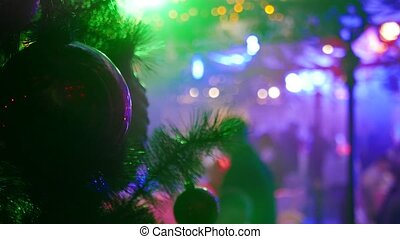 Christmas and New Year decoration and blured lights and people in the background. Changing color glowing background