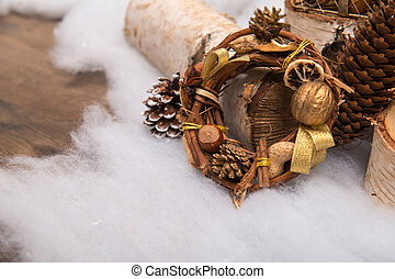 Christmas tree toys and decoration like fir branch wooden log and pine and fir cones and wreath of nuts hazel peanuts on snow with copy place