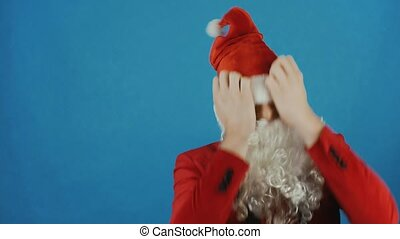 Christmas and New year, man like a Santa Claus pulled hat over his eyes, blue background