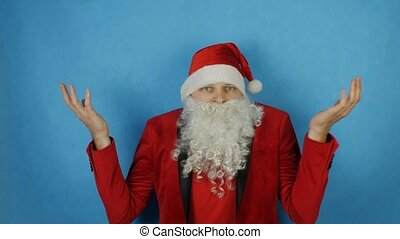 Christmas and New year, man like a Santa Claus surprised and shocked, on blue background