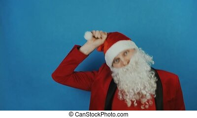 Christmas and New year, man like a Santa pulls himself on his hat or cap, on blue background