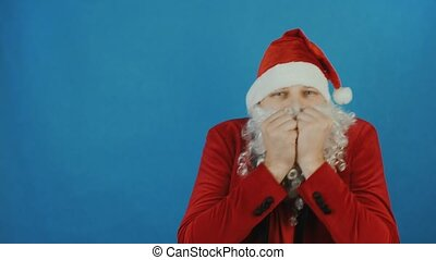 Christmas and New year, man like a Santa trembles or freezes from the cold, on blue background