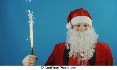 Christmas and New year, man like a Santa with handheld fireworks candle or sparkler, blue background
