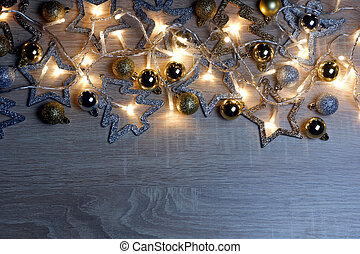 Christmas and New Year template with christmas decorations, gold and silver shiny, matte and sparkling christmas balls and garland of yellow led lights on light oak wood background with copy space