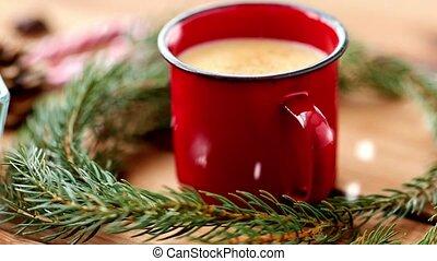 christmas and seasonal drinks concept - snow falling over red mug of eggnog and fir branch on table