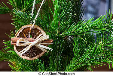 Christmas arrangement of dry orange slices and cinnamon sticks on the Christmas tree