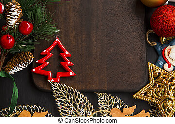 Christmas arrangement with ornaments and decoration on wooden board top view with tree ornaments, pine branches, balls