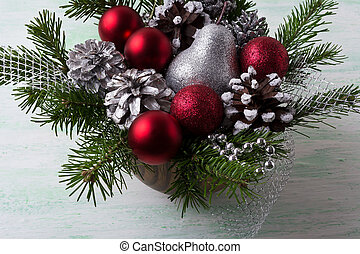 Christmas arrangement with red baubles and decorated pine cones