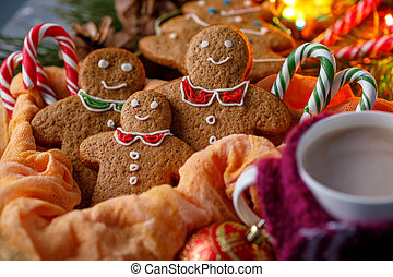 Christmas atmosphere of magic. Gingerbread and hot cocoa in a cup with a cheerful scarf. Funny smiling little men and candy canes.