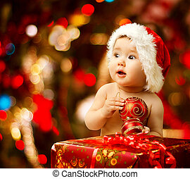 Christmas baby in santa hat near red present gift box -...