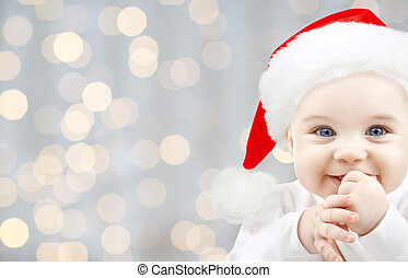 happy baby in santa hat over holidays lights