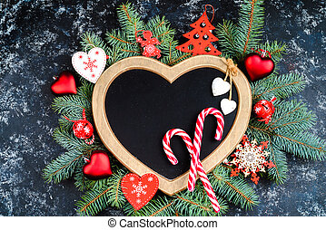 christmas background - decorations and fir branch on a table, a frame in the shape of a heart, top view, place for text, flat lay, christmas card