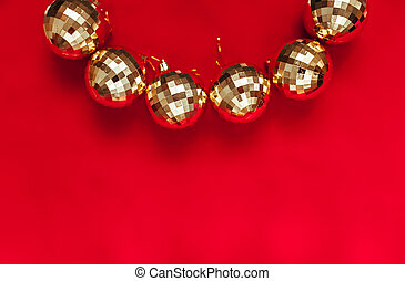 Golden balls on red background with place for text.