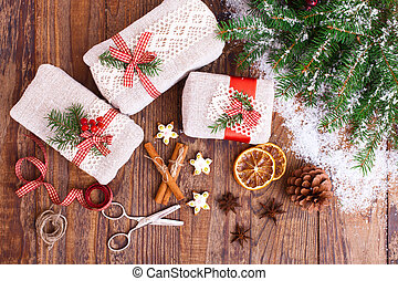 Handmade gift boxes near Christmas tree with cookies and spices.