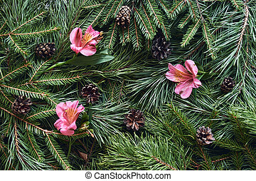 Christmas background of green spruce and pine branches, with cones and flowers.