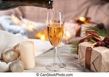 Christmas background with a bottle filling a glass of champagne on a light background.