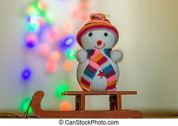snowman sitting on a sled