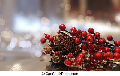 Christmas background with berries and pine cones against a bokhe light background