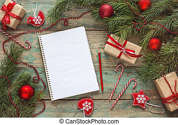 Christmas background with blank notebook, fir branches, decorations and  gift boxes. Christmas to-do list or wish list. .Top view.