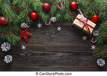 Christmas background with border from pine branches and decorations on dark wooden table. Space for text.