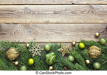 Christmas background with border of fir branches and decorations on old wooden table. Space for text or design.